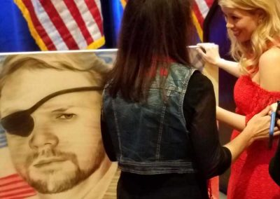 Tara Crenshaw and shen with Dan Crenshaw portrait